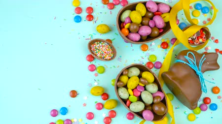 açucarado : Happy Easter decadent chocolate background overhead with Easter eggs and candy on a rustic wood background with copy space.
