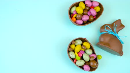 słodycze : Happy Easter decadent chocolate background overhead with Easter eggs and candy on a rustic wood background with copy space.