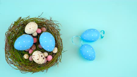 Happy Easter overhead with Easter eggs and decorations on a wood table background time lapse, Стоковые видеозаписи