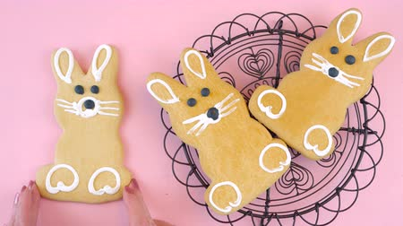 vasárnap : Happy Easter overhead with Easter bunny cookies and candy on a wood table, time lapse. Stock mozgókép