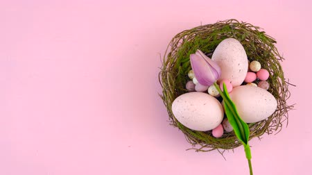 Happy Easter overhead with Easter eggs and decorations on a wood table background with copy space.