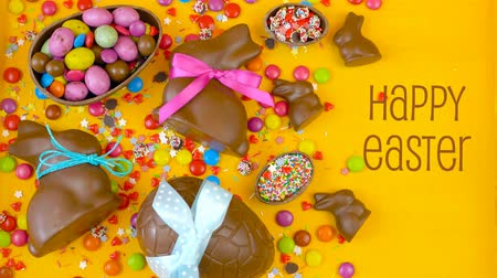konfekció : Happy Easter decadent chocolate background overhead with Easter eggs and candy on a rustic wood background with copy space.