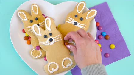 Happy Easter overhead with Easter bunny cookies and candy on a wood table, time lapse. Стоковые видеозаписи