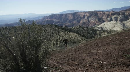 fisher : slow motion man running up steep trail in desert