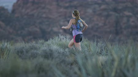 pan shot : slow motion of girl trail running in desert