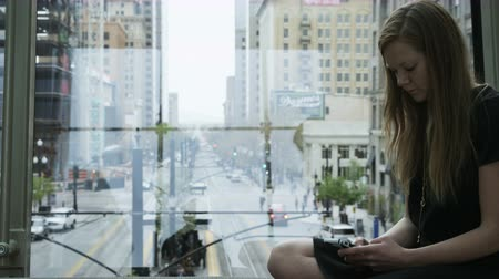 sending : girl texting overlooking downtown city scape