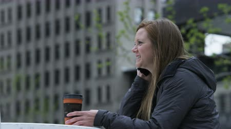 sending : woman enjoying coffee while talking on cell phone in city