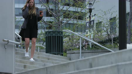 sending : woman on cell phone with coffee walking through city