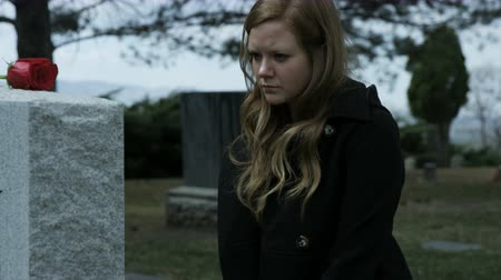 gravestone : slow motion somber girl leaving rose on grave stone in cemetery Stock Footage