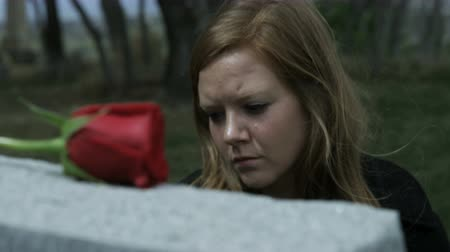 gravestone : slow motion somber girl visiting grave stone in cemetery