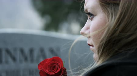 loved : slow motion somber girl leaving rose on gravestone in cemetery