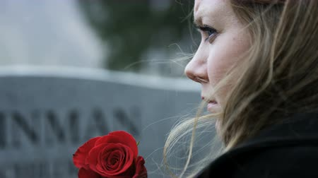 надгробие : slow motion somber girl with rose visits gravestone in cemetery