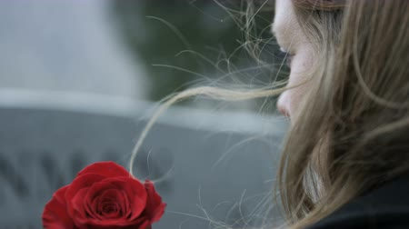 loved : slow motion somber girl with rose visits gravestone in cemetery