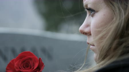 могильная плита : slow motion somber girl with rose visits gravestone in cemetery