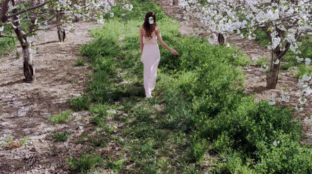 smelling : slow motion woman walking through orchard covered in white blossoms