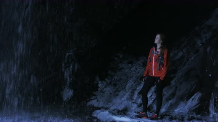 kaland : slow motion girl looking at waterfall in frozen cave