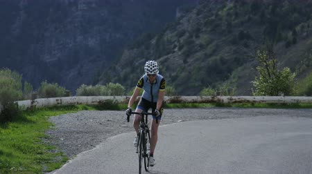 wspinaczka górska : Woman road biking through mountains Wideo