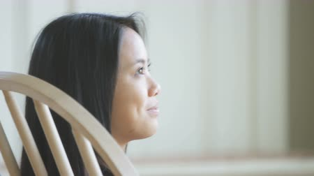 nurture : Asian woman in rocking chair looking down Stock Footage