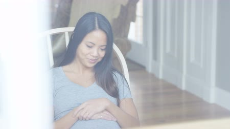 nurture : Pregnant asian woman in rocking chair holding belly
