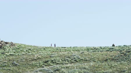 ridge line : Couple hiking in distance through desert