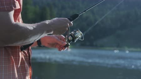 rúd : Man reeling in fishing line while fishing