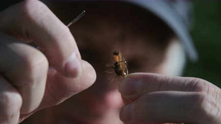 close up of man prepping fishing fly Stock Footage