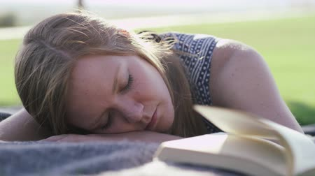 girl in park sleeping on book