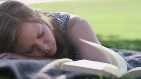 recreational park : woman in park sleeping next to open book Stock Footage