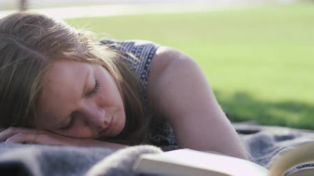 woman in park sleeping next to open book Stock Footage