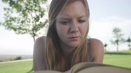 breezy : close up of woman reading book in park