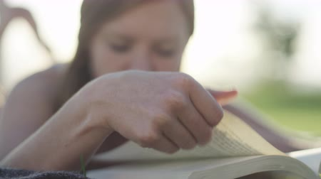close up of a woman reading a book outside