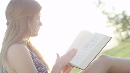 woman in park reading a book Stock Footage