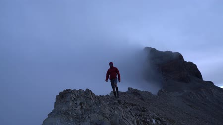 ürpertici : man walking across a foggy mountain ridge while wind blows