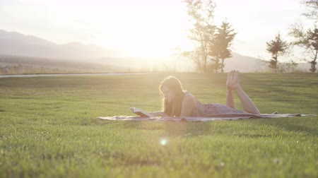 breezy : woman laying in grass reading a book