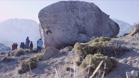 man makes hard moves on boulder problem in California desert