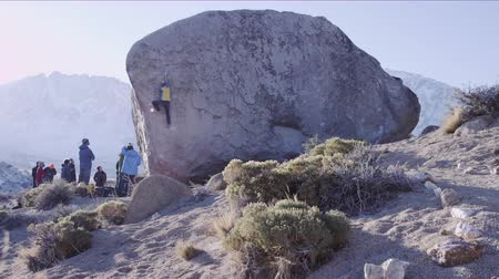 piskopos : man climbs up boulder problem while group watches him from below