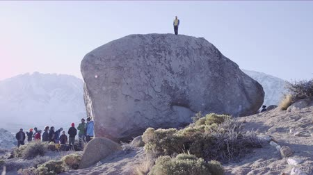 bouldering : man stands on top of boulder after sending the climb Stock Footage