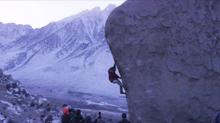ascend : man climbing on boulder with group of climbers below Stock Footage