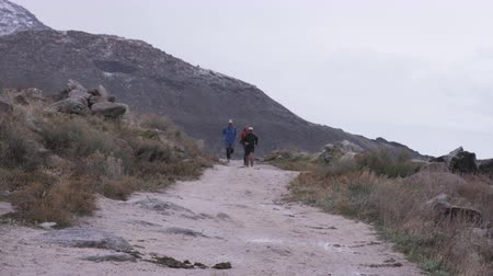 group of runners runs down trail in cold weather at Antelope Island in Utah