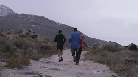 shot of runners running down trail, rabbit runs in front of them at Antelope Island in Utah Stock Footage