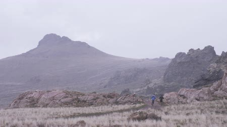 antilopa : wide shot of two men running on trail while snow begins to fall