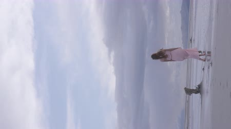 go away : vertical shot of woman walking down beach in pink dress
