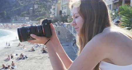fotky : girl taking photos on beach in Italy