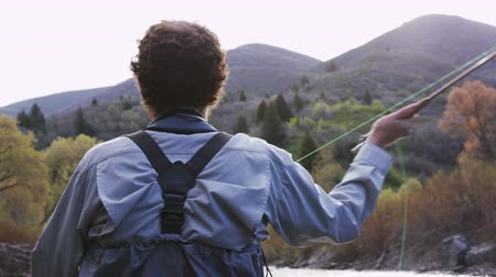 fishing pole : man casting as he fly fishes in Utah river