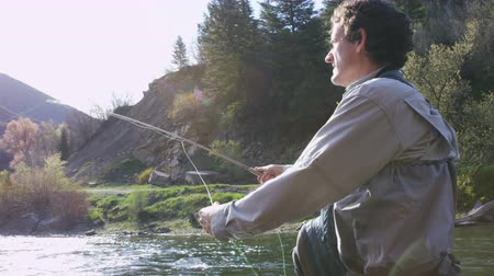 outdoor hobby : medium shot of man fly fishing in river Stock Footage