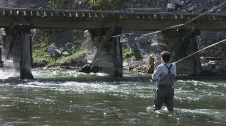 fishing pole : man fly fishing next to old bridge