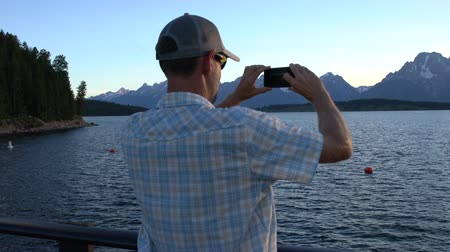 здесь : man taking photo of mountains with is cell phone in the Tetons