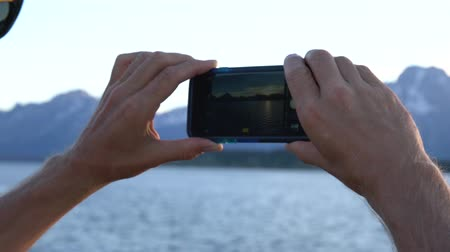 grand tetons : over the shoulder of man taking picture of Tetons on cell phone Stock Footage