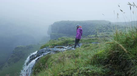 tilt down : Woman walks to the edge of waterfall in Iceland, takes in view