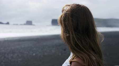 authenticity : woman on black sand beach looking towards horizon